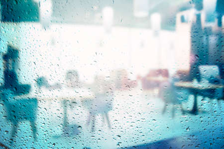 Blurred look at the restaurant through the rain window background of modern cafe restaurant table blur background with bokeh light. leisure lifestyle