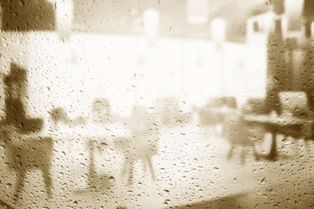 Blurred look at the empty restaurant through the rain window background of modern cafe restaurant table blur background with bokeh light. leisure lifestyle