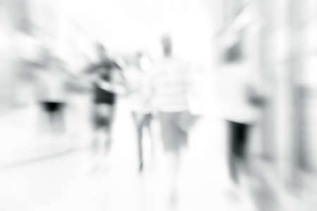 Blur store with bokeh luxury background. Silhouettes of Business People in Blurred Motion Walking. Business people walking in the office corridor. anonymous People standing and walking on a trade show booth, generic background with a blur effect applied 免版税图像