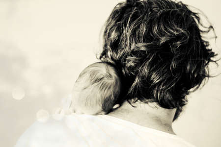 Blurred Newborn baby and dad. Happiness Baby on the fathers hands. Father with baby sleeping over his shoulder. Dark background.