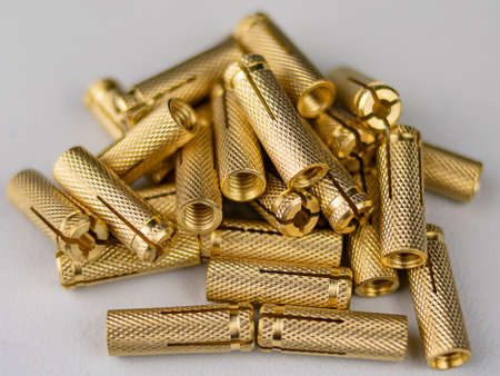 Heap of shiny metal studs on white background Imagens