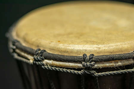 Close-up of a djembe of natural skin of African origin with its tightly fastened tension and tuning strings