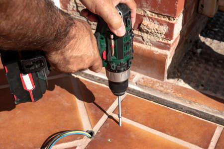 A worker is screwing a threaded rod with a drill and cordless screwdriver into a metal block previously fixed to the ground