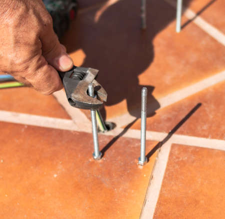 Worker tightens a nut on a threaded rod fixed to the ground on a sunny day and with other tools
