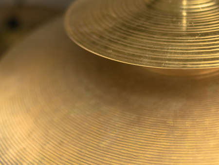 Splash and crash plates of a drum, both bright and golden, hammered and with grooves for sound diffusion
