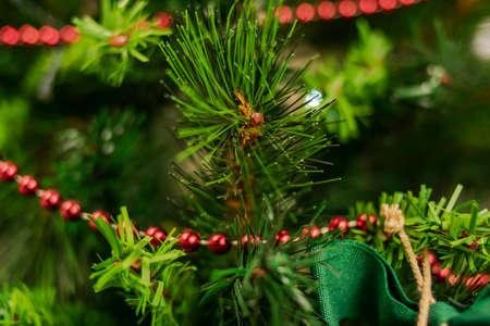 Un ramo di abete sopra le decorazioni dell'albero acquista risalto Archivio Fotografico