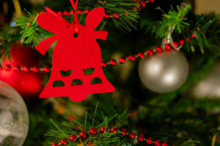 Christmas bell hangs on the Christmas fir branch between silver and red colored balls and a chain of small red balls. Archivio Fotografico