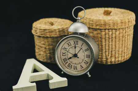 Alarm clock with two wicker boxes and a capital letter A in matt white and corporeal wood