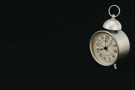 Classic and vintage matt gray alarm clock, marking eight oclock, on a black background and slightly turned