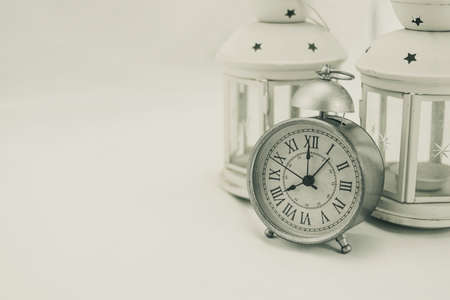 Classic gray alarm clock with two white lanterns candle holders on white background