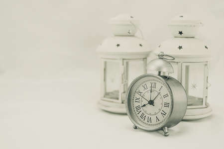 Classic matt gray clock marking eight oclock a day, along with two vintage candle lanterns behind it and white background
