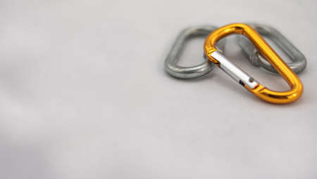 Climbing carabiners, two gray and one orange, on impure white background Фото со стока