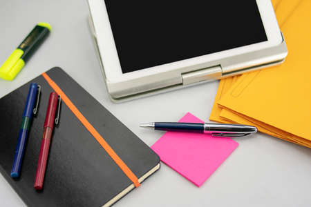 Office supplies consisting of tablet with keyboard, fluorescent marker, red and blue markers, modern pen, sticky notepad and note book Stok Fotoğraf