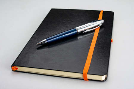 Bound notepad with black hardcover and modern blue and silver pen