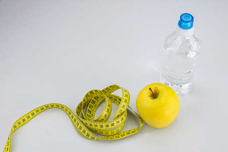 Yellow apple, water bottle with blue cap and yellow measuring tape with black numbers on white background