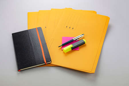 Pen and fluorescent marker on fuchsia memo note, yellow subfolders and notebook Banco de Imagens - 132123863