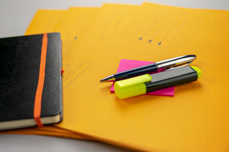 Pen and fluorescent marker on memo note, yellow subfolders and notebook
