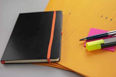 Note pad with pen, fluorescent marker and yellow subfolders