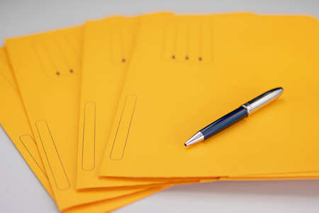 Office supplies consisting of a modern pen on yellow subfolders