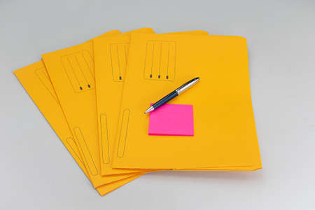 Modern ballpoint pen with fuchsia notepad on yellow subfolders on white background