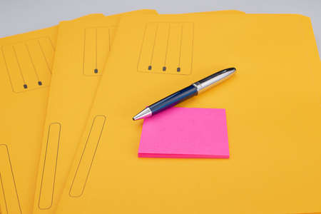 Office supplies consisting of modern pen and fuchsia notepad on yellow subfolders Фото со стока