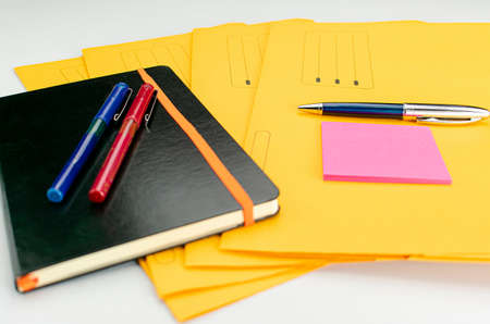 Office supplies consisting of fluorescent marker, red and blue markers, modern pen, sticky notepad and note book on yellow subfolders