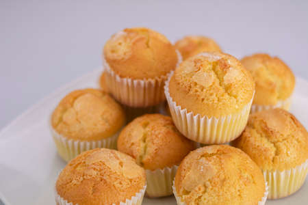 Delicious golden muffins covered with freshly baked sugar on a white square plate on a white background