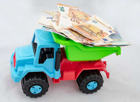 Colorful plastic truck carries a large number of 50 and 20 Euro bills on top of it