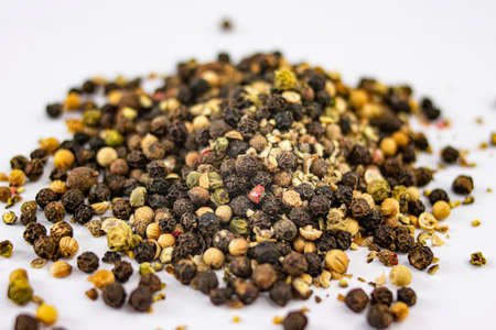 Pile of different types of peppercorns to season cooking recipes over white background