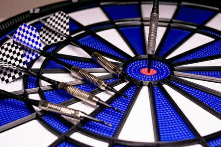 Traditional game of darts composed of target and darts in white and blue colors, with central point in red, and plastic material to avoid dangers and injuries in children