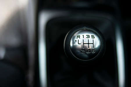 Close up view of a gear lever shift. Manual gearbox. Car interior details. Car transmission. Soft lighting. Abstract view. European car