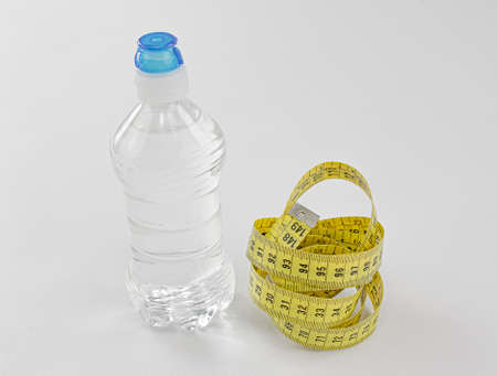 Bottle of mineral water without gas with sports cap and measuring yellow tape as essential elements for a diet