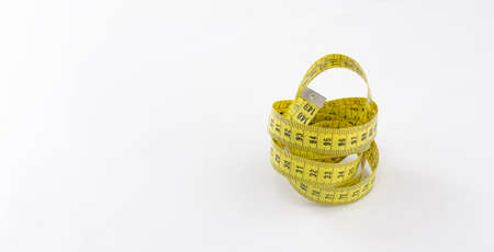 Yellow tape measure with black numbering rolled on itself and metallic terminal over white background