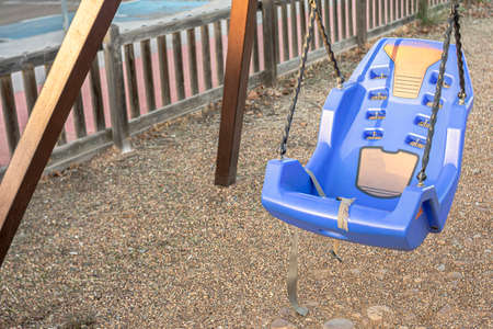 Plastic safety seat with belts for children and people with disabilities on a playground swing. Sand and cobblestone floor