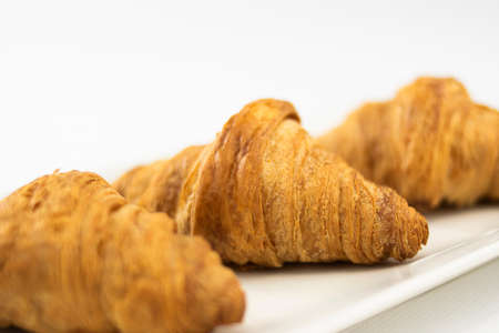 Three croissants on a plate focused on the center one on white background