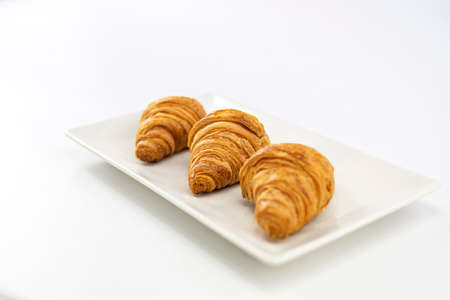 Side view of three delicious freshly made croissants and placed on a white plate on white background
