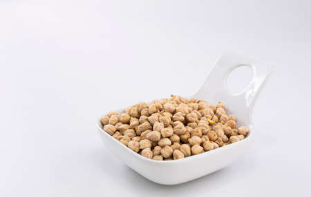 Clean and raw chickpeas placed in a white bowl on a white background ready to be cooked by a cook according to a recipe.