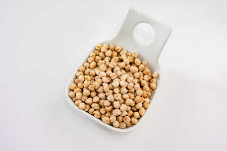 Aerial view of a plate of raw chickpeas ready to cook them in a kitchen recipe. Food or ingredients