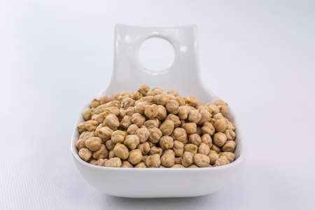 Raw chickpeas in a white bowl ready for cooking in a culinary recipe
