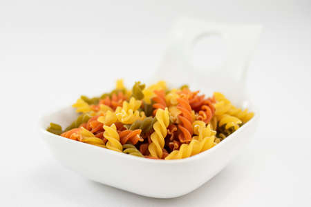 Macro of white bowl of colorful pasta made with vegetables on white background