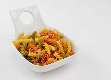 white dish of colorful pasta made with vegetables on white background