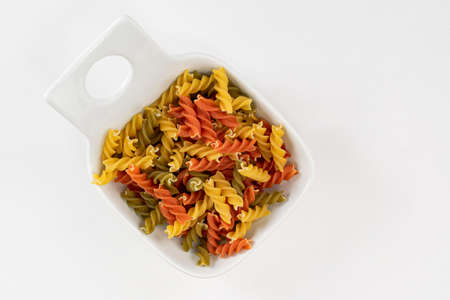 A bowl of colorful raw pasta made with vegetables  to boil and serve aldente