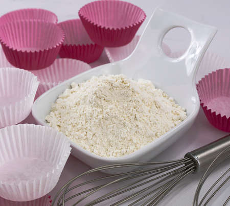 flour in a white bowl, whipping rods and paper bases for muffins on white background Stok Fotoğraf