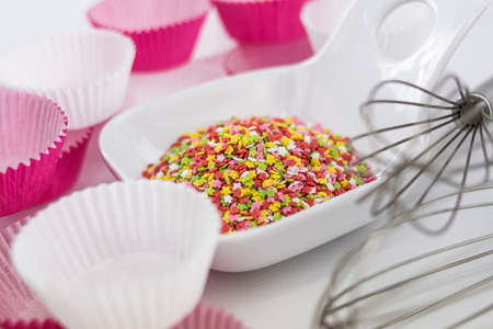 Decorative sugar colored stars in two white bowls, whipping rods and paper cupcake bases on white background