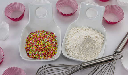 Pile of wheat flour and decorative sugar stars in two bowls with rods to beat eggs and white and pink paper molds for muffins