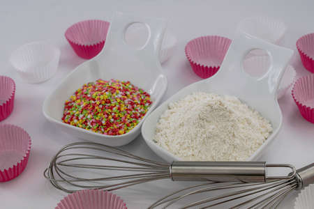 white flour and colored sugar stars in two white bowls, whipping rods and paper bases for muffins on white background