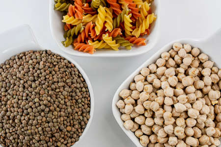 Three white bowls with legumes such as lentils and chickpeas and pasta with colorful vegetables
