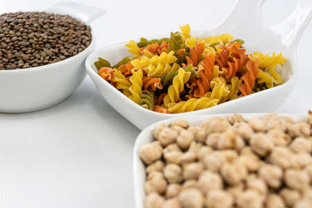 Close up view of colorful pasta, chickpeas and lentils in white bowls on white background