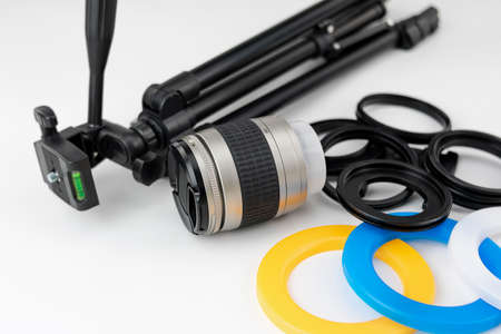 Small tripod, camera lens, color filters and adapter rings on white background Stok Fotoğraf