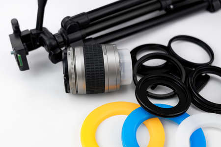 Lens for photo camera, small tripod and adapter rings with color filters for circular flash